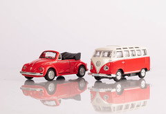 A classic red minibus and red beetle car