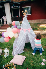 A child standing in front of a teepee. Easter picnic