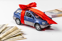 Metal car model with bow and red gift ribbon on white background with dollars