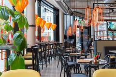 Modernes Interieur in dem Kölner coa Wok & Bowl Restaurant mit orangen Lampen, gelben Stühlen und grünen Pflanzen