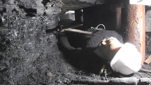 A miner hacking the coal in the lying down position because of the thin coal seam at Arigna Mining Experience
