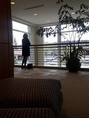 Woman talking on a cell, purse, office building, large windows, potted plant, sofa, railing, carpet, tile, Bel-Red Road, Bellevue, Washington, USA