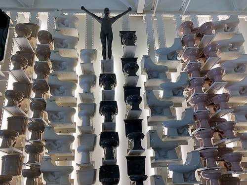 Wall of toilets with nude male mannequin, Kohler Design Center, Kohler, Wisconsin