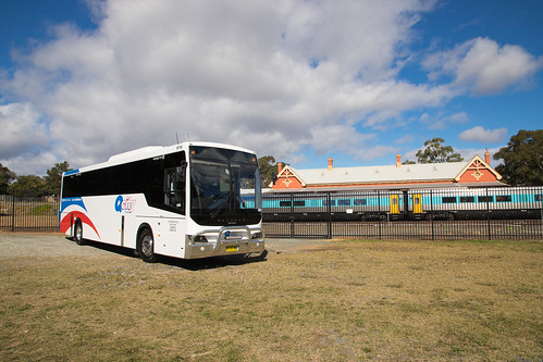 QCity (8718) Volvo B7R/Volgren Endura parked near the Queanbeyan Rail Station while a Sydney bound 'Xplorer' service makes a station stop