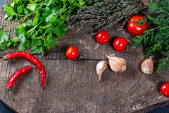 Fresh vegetables and herbs on old wooden background