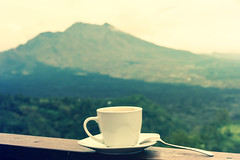 White cup of hot coffee on nature background. Bali island. Volcano Batur.