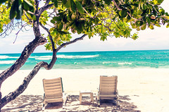 Chaise lounges on the beautiful tropical beach with white sand. Bali island. Indonesia.