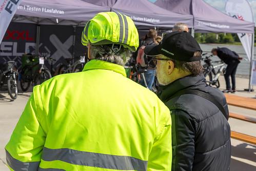 Mann in gelber Warnjacke und reflektierendem Helmschutz für eine bessere Sichtbarkeit und mehr Sicherheit beim Radfahren