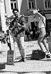 """""""Dancing"""" woman photographer around a street musician"""