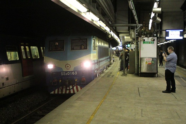Electric locomotive SS8 0163 leads a northbound through train through Mong Kok East station