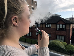 A woman blowing smoke out of a vape pen, stock photo