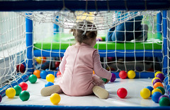 A girl playing with colourful balls in a playroom