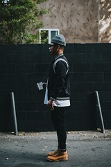 man standing near wall holding a cup looking forward - Credit to https://myfriendscoffee.com/