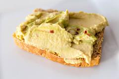 Ausgewogener Brotaufstrich mit Avocado-Hummus und Gewürzen, isoliert vor weißem Hintergrund