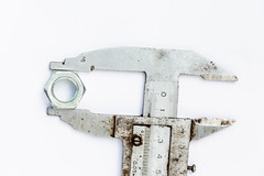 Old wrench with iron nut on white background