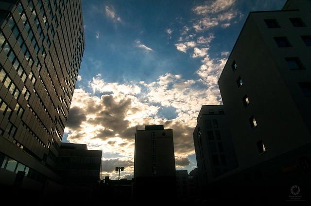 Innerstädtische Abendstimmung mit mehreren Hochhäusern gegen die untergehende Sonne.