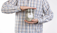 Man in shirt holding money jar