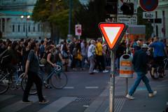 Leuchtendes Verkehrszeichen Vorrang gewähren mit einer vorbeigehenden Menschenmenge im Hintergrund