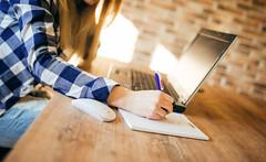 Geschäftsfrau sitzt am Laptop und schreibt auf Notizblock mit Stift