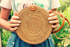 Woman hands with stylich eco friendly rattan bag on a tropical background. Bali island.