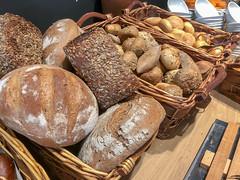 Bäckereiauslage am Frühstücksbüfett, mit verschiedenen Broten, Vollkorn-Brötchen mit Kernen und normalen Brötchen, in einfachen Holzkörben