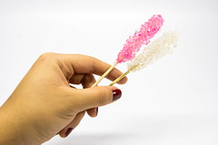 Hand holding pink and white rock candy