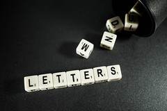 Dice reading LETTERS on a black surface