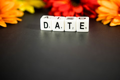 Dice reading DATE with flowers on the background