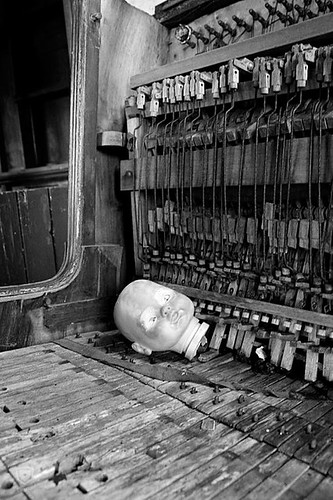 dolls head on abandoned piano
