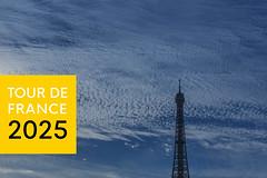 """Die Spitze des Eiffelturms vor bewölktem Himmel und neben der Aufschrift """"Tour de France 2025"""", für das erfolgreiche Radsport-Event in Frankreich"""