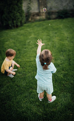A brother and a sister playing with bubbles on the grass