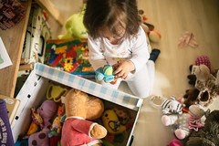 A little girl playing with lots of colorful toys. Turtle toy in baby's hands