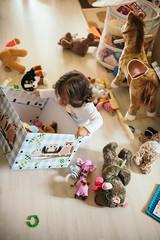 Kleines Mädchen druchstöbert Kiste nach Stofftieren