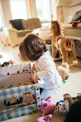 A little girl looking for a toy in a box
