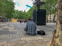 """Obdachloser Mann sitzt auf dem Neumarkt, vor Besucher des Kölner Kunstfestivals """"Impulse Theater"""""""