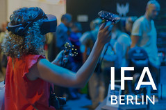 """Woman with VR-Glasses on a Computer fair, next to picture title """"IFA BERLIN"""""""