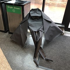 Giant caped origami guy sitting in a chair after the convention