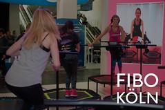 """Frauen beim Jumping Fitness auf Trampolins mit Sportrainerin, neben dem Bildtitel """"Fibo Köln"""""""