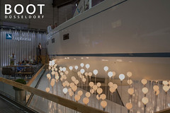 """Euphoria Yacht on a german boat fair in artistic design due to shining lamps, next to the picture title """"Boot Düsseldorf""""."""