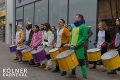 """Trommelgruppe in Tierkostümen stehen vor einem Geschäft in der Fußgängerzone und machen Musik, neben dem Bildtitel """"Kölner Karneval"""""""
