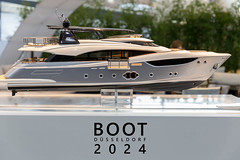 "Miniature replica of a luxury yacht, exhibited at the German boat fair next to the title ""Boot Düsseldorf 2024"""