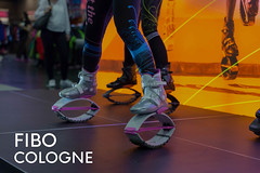 """Sports fair visitors test Kargo Jumps with futuristic looking jumping shoes for fitness training, next to the picture title """"Fibo Cologne"""""""