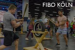 """Fitnessmessebesucher beim Krafttraining am funktionalen Allzweck Fitnessgerät Scape Goat, neben dem Bildtitel """"Fibo Köln"""""""