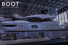 "Multi-storey luxury yacht presented at a German boat show, next to picture title ""Boot Düsseldorf"""