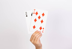 Hand holding deuce and seven playing cards