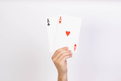 Hand holding two aces playing cards