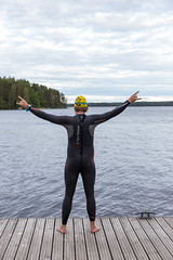 Man from behind with extended arms, in neoprene suit , swimming cap and diving goggles on a wooden jetty at Lake Päijänne in Finland