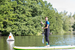 Man with paddle on a stand-up paddleboard, doing water sports on a lake in Finland