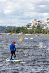 Water sportsman on a stand-up paddleboard at the edge of the swimming contest for the Finnish Ironman 70.3, observing triathletes in the lake