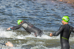 Close-up of Ironman swimmers jumping heads first into a lake for the first triathlon discipline and create water splashes